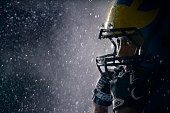 American football player in a haze and rain on black background. Portrait close-up