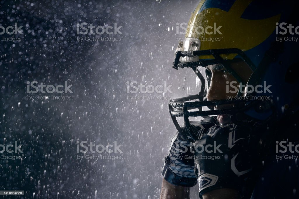 American football player in a haze and rain on black background. Portrait close-up stock photo