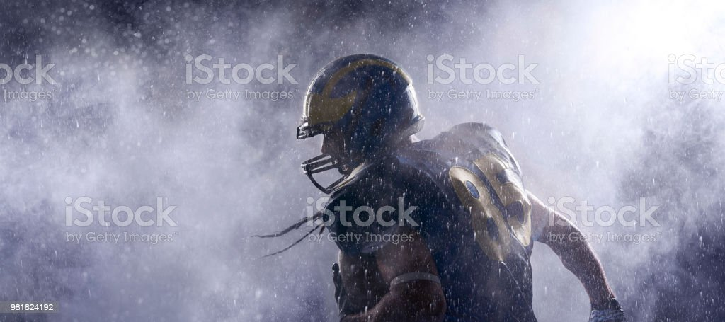 American football player in a haze on black background. Portrait stock photo