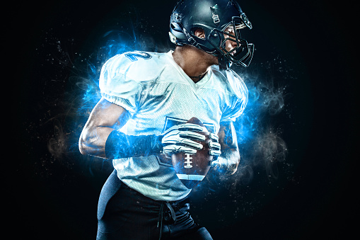 American football player in helmet with ball in hands. Fire background. Team sports. Sport wallpaper.
