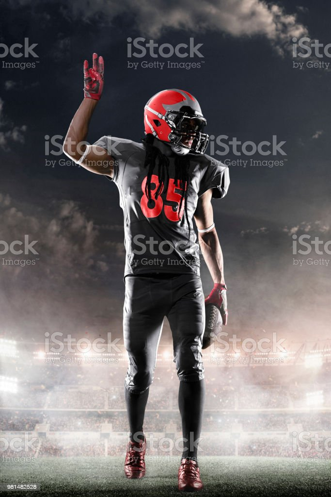 American football player in professional night sport stadium with...