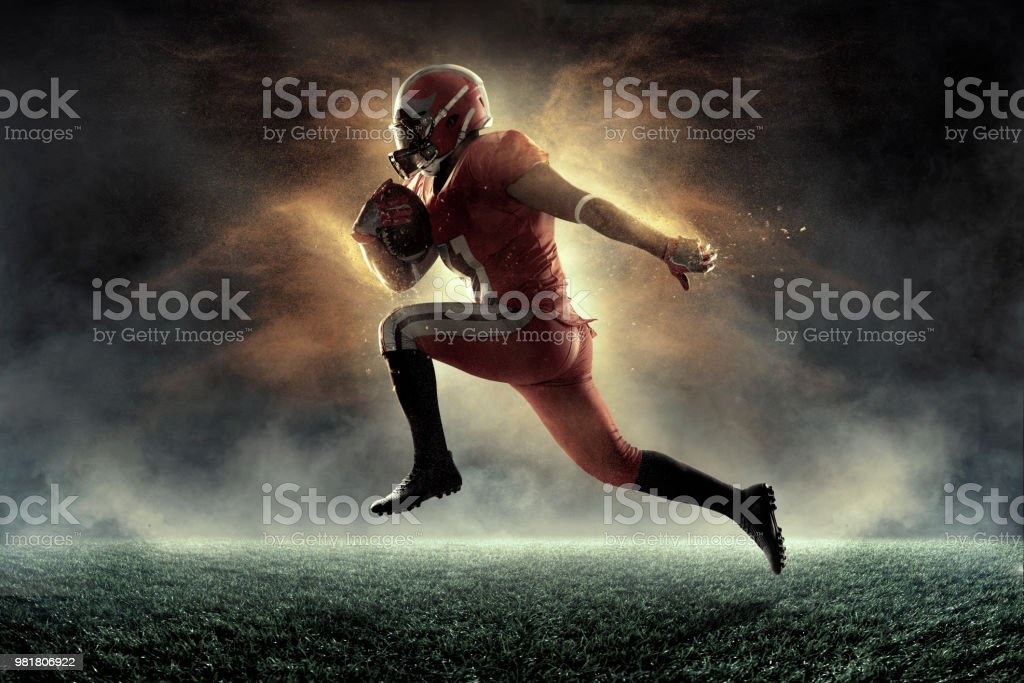 American football player jumps and catches the ball in flight in...