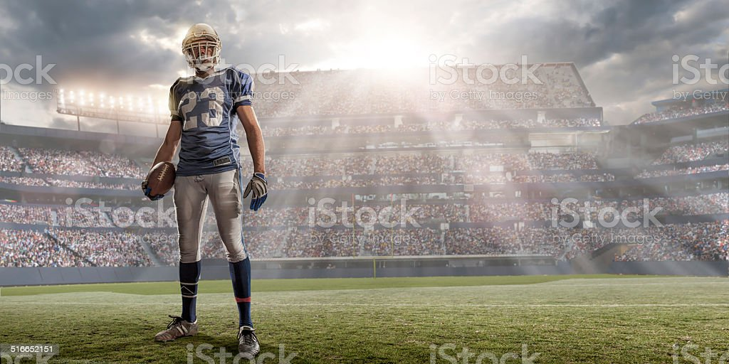 American Football Player in Sunlit Stadium stock photo