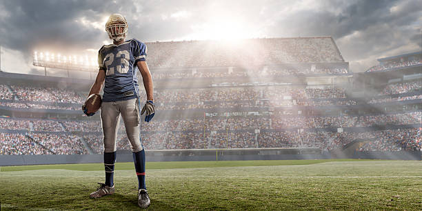 american football player in sunlit stadium - american football player stock photos and pictures