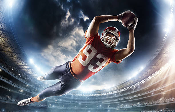 American football player jumping Wide angle low view of an American Football player jumping with a ball in the end zone for a touchdown. The action takes place on professional stadium. The player wears unbranded sports uniform. wide receiver athlete stock pictures, royalty-free photos & images
