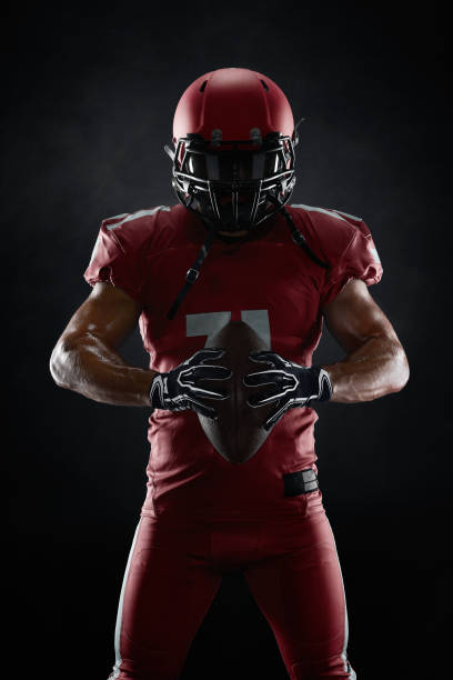 american football player on dark background - american football player stock photos and pictures