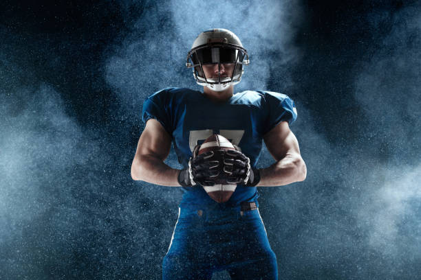 American football player on smoke background American football player american football uniform stock pictures, royalty-free photos & images