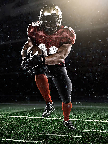 American football player A male american football player makes a dramatic play. The stadium is dark behind him. line of scrimmage stock pictures, royalty-free photos & images