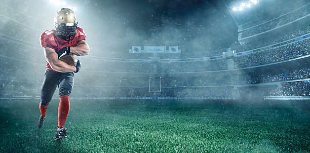 American football player A male american football player makes a dramatic play. The stadium is dark behind him. Only the lights of the stadium shine brightly, creating a halo effect around the bulbs. line of scrimmage stock pictures, royalty-free photos & images