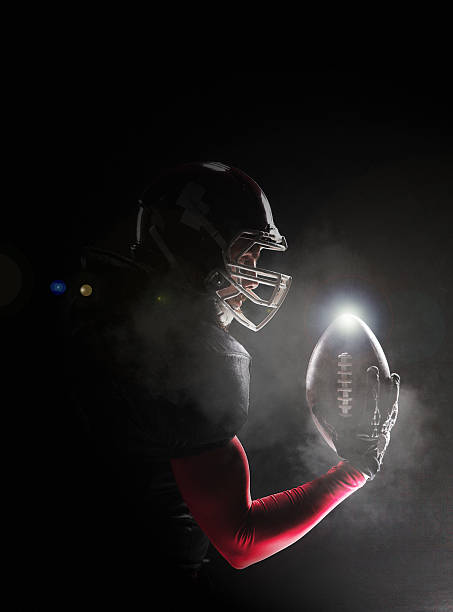 american football player posing with ball on black background - american football player stock photos and pictures