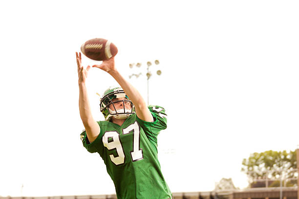 American Football Player Receiver in Action American football player receiving a pass, Midwest, USA. wide receiver athlete stock pictures, royalty-free photos & images