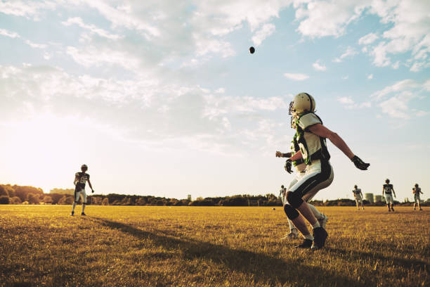 American football player running for a pass during practice American football players running to catch a pass during team practice drills on a football field in the afternoon wide receiver athlete stock pictures, royalty-free photos & images