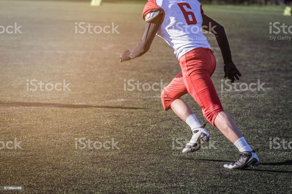 American football player running on the field stock photo