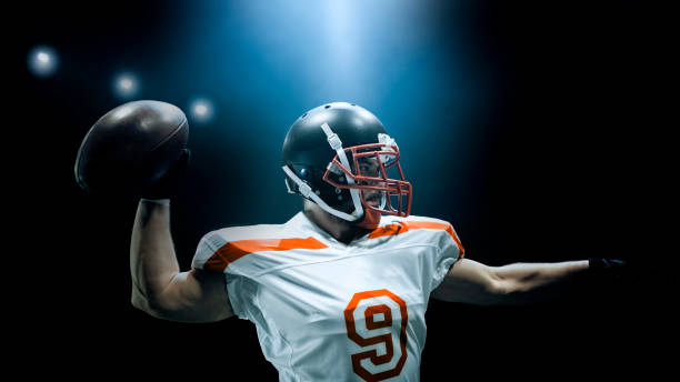 American football player throwing ball American football player throwing ball against black background. quarterback stock pictures, royalty-free photos & images
