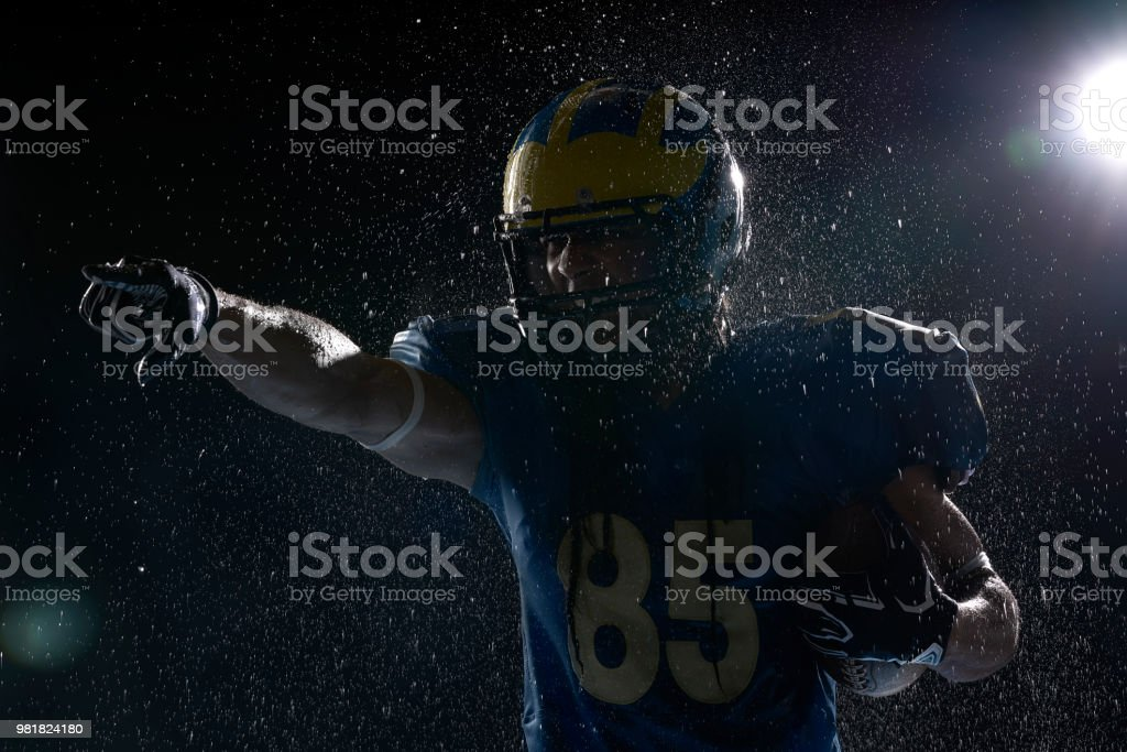 American football player with ball in a water drops on black background. Portrait