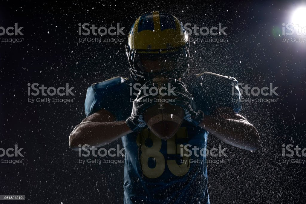 American football player with ball in a water drops on black background. Portrait stock photo
