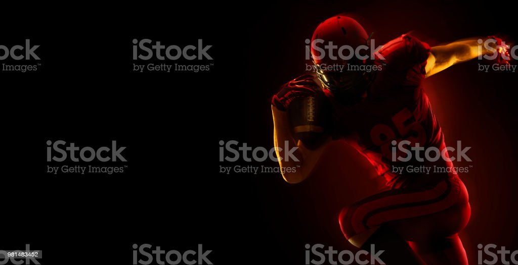 American football player with ball on a dark red background stock photo