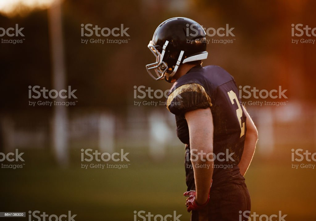 American football player with her arms akimbo on a playing field. royalty-free stock photo