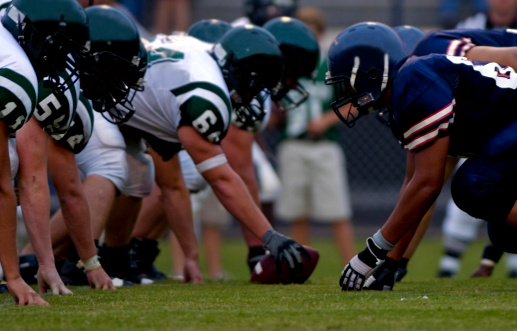 American Football Players At Line Of Scrimmage During Football Game Stock Photo - Download Image Now