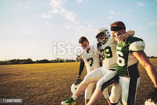 American football players carrying an injured teammate off the field during a practice session in the late afternoon