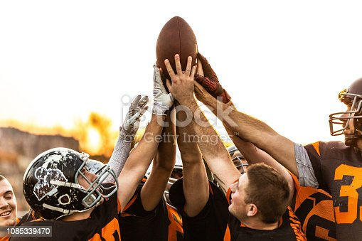 American Football Players Celebrating The Victory all together with raised hand in the air