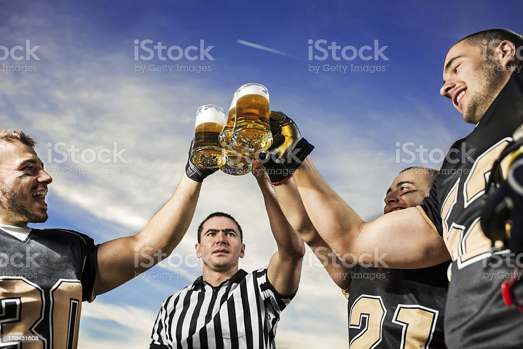 American Football Players celebrating victory with beer. royalty-free stock photo