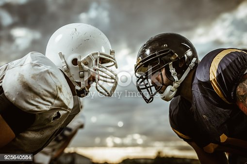 Two American football players looking at each other on a beginning of the match.