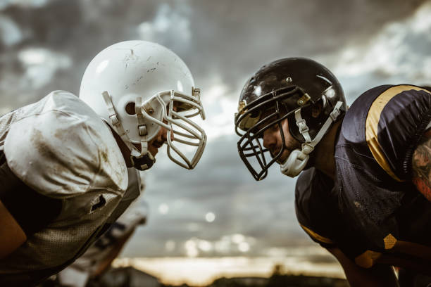 American football players confronting before the beginning of a match. Two American football players looking at each other on a beginning of the match. face to face stock pictures, royalty-free photos & images