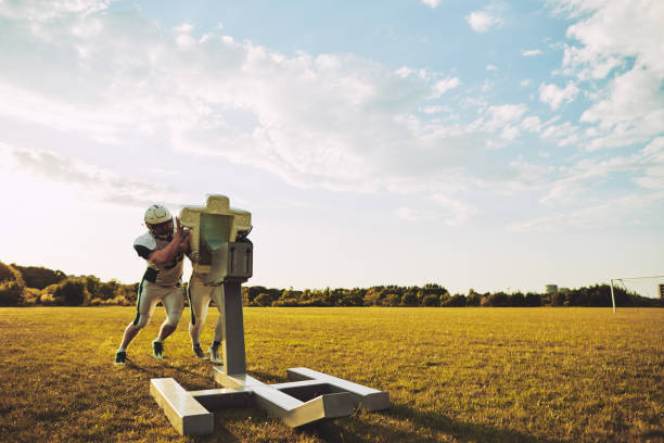 American football players doing tackling drills together during practice Two American football teammates practicing tackles and defensive drills with a sled outside on a sports field in the afternoon practicing stock pictures, royalty-free photos & images