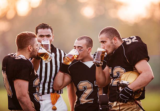 american-football-spieler, trinkt bier. - bier gesund stock-fotos und bilder