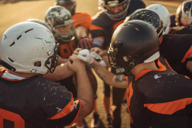 American Football Players Huddling American Football Players Huddling During Time Out american football uniform stock pictures, royalty-free photos & images