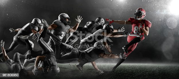 American football players fights for the ball in dark sport stadium with fog. The winner is forging ahead