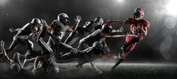American football players in dark sport stadium American football players fights for the ball in dark sport stadium with fog. The winner is forging ahead american football uniform stock pictures, royalty-free photos & images