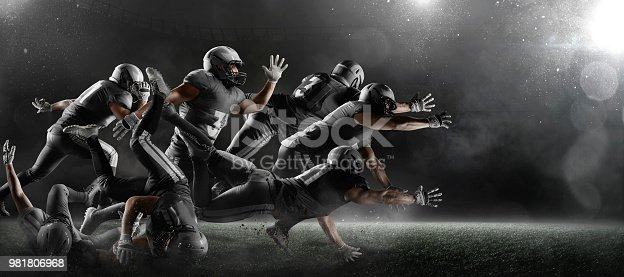 American football players fights for the ball and fall in dark sport stadium with fog. Sport team are dressed in black uniform