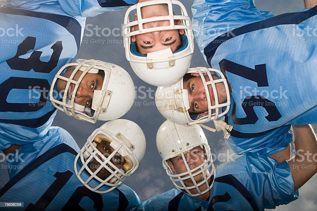 American football players in huddle stock photo