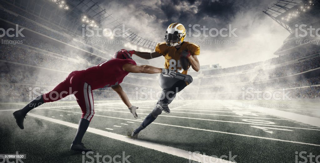 American football players fight for the ball in professional sport...