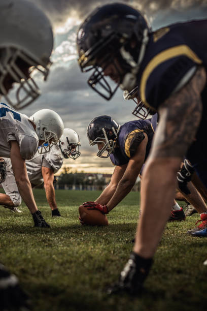American football players on a beginning of the match. American football players confronting before the beginning of a match. football lineman stock pictures, royalty-free photos & images