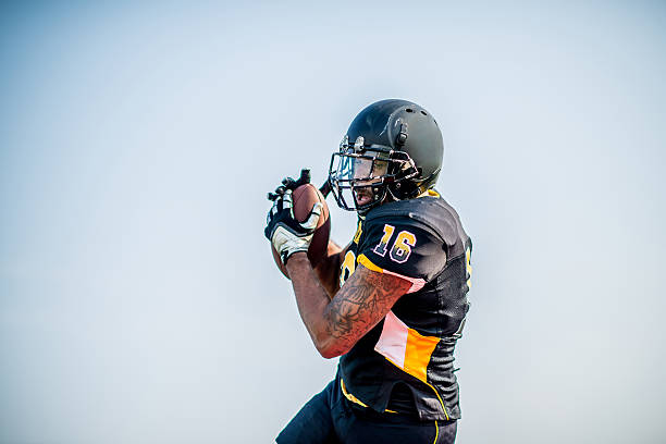 American Football Players American football players on the field in action. wide receiver athlete stock pictures, royalty-free photos & images