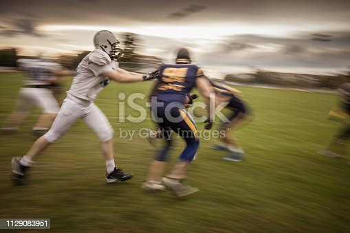Group of American football players having a sports match on a playing field. Blurred motion.