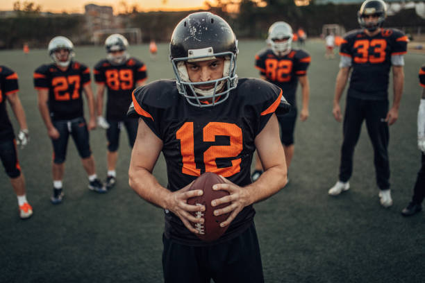 American football players portrait Young men with American football uniform and football helmet standing on sport court, looking at camera. american football uniform stock pictures, royalty-free photos & images