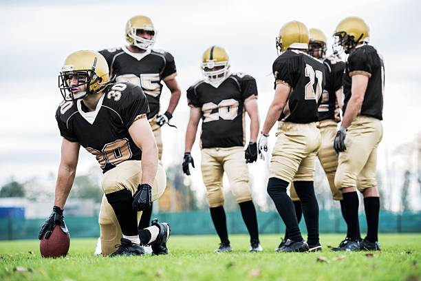 American football players positioning. American football players taking their positions. line of scrimmage stock pictures, royalty-free photos & images