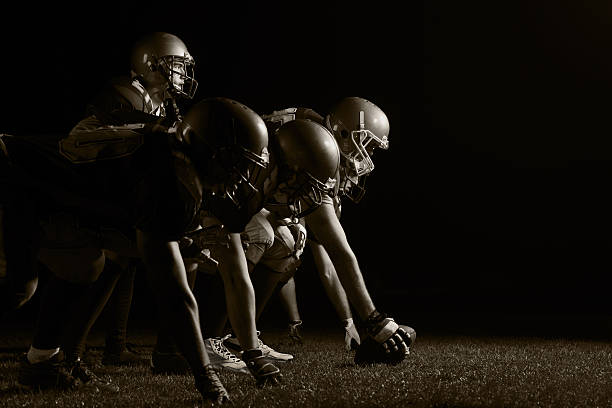 American football players positioning. American football players starting a match. Black and white.   football lineman stock pictures, royalty-free photos & images