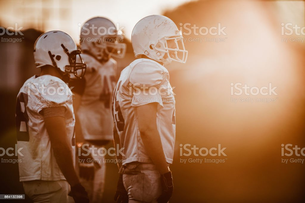 American football players standing in the field at sunset. royalty-free stock photo