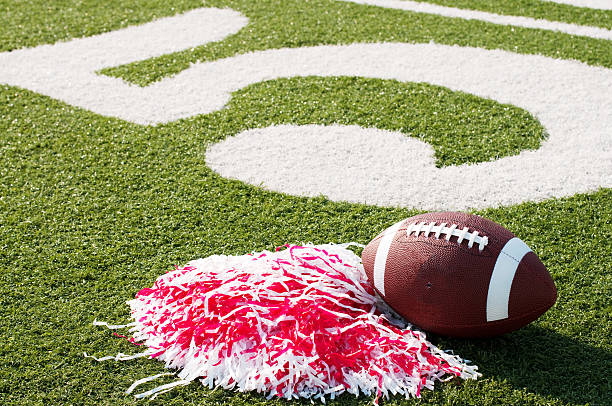 american football, red pompom on field with painted number 5 - pompon stockfoto's en -beelden