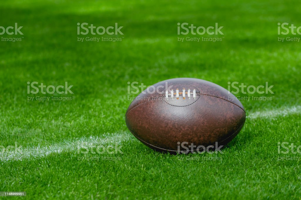 American football, rugby ball on green grass field background