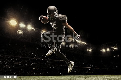 Professional american football player on stadium running in action. Sport wallpaper with copyspace. 3D model of the stadium was created by me (the author)