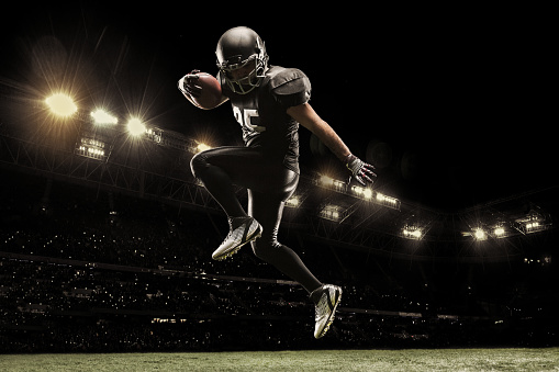 istock American football sportsman player on stadium running in action. Sport wallpaper with copyspace. 1133824188