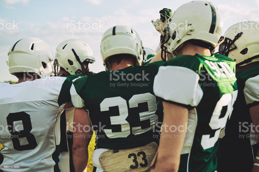 American football team huddling together before a big game stock photo
