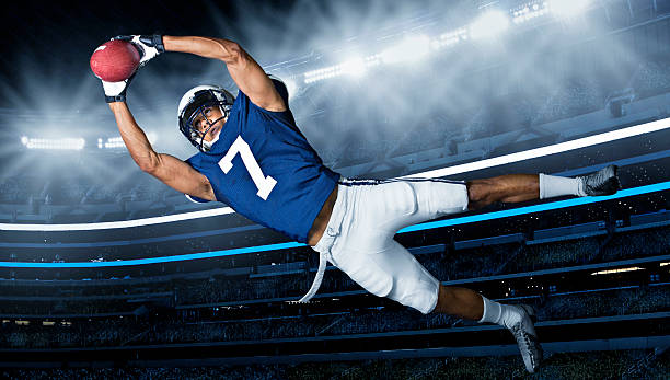 American Football Touchdown Catch An american football player diving through the air to catch the ball and score a touchdown. Live game action in a big stadium catching stock pictures, royalty-free photos & images
