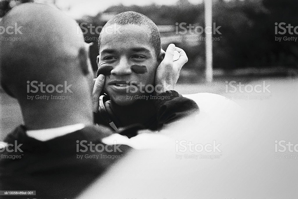 American footballer painting team-mates face, outdoors (B&W) Lizenzfreies stock-foto